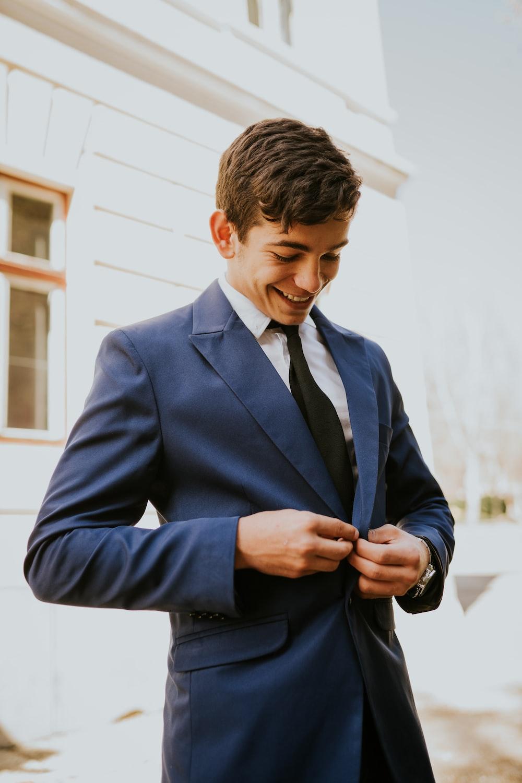 smiling man buttoning his blazer