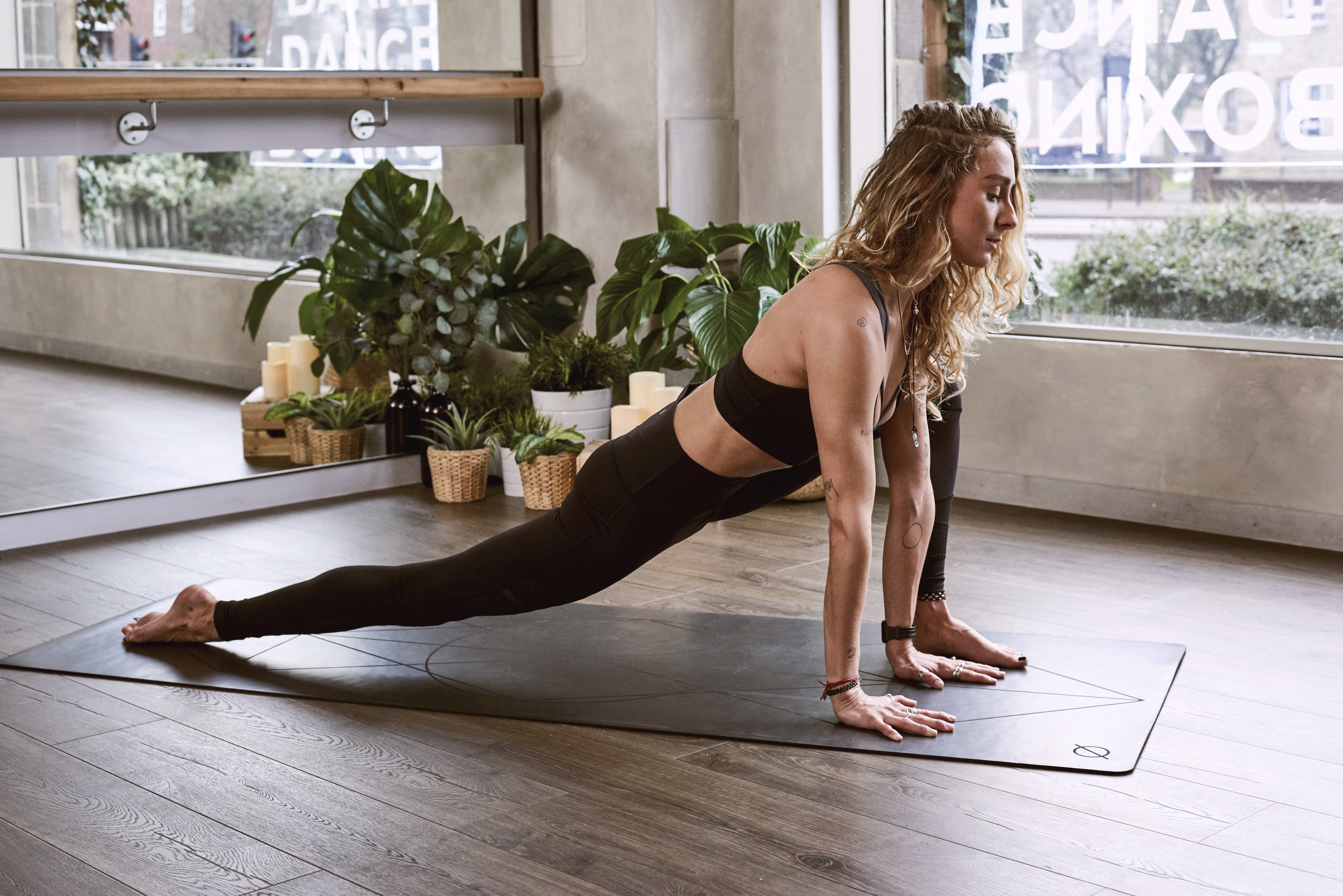 woman in black yoga pants and top doing yoga near window