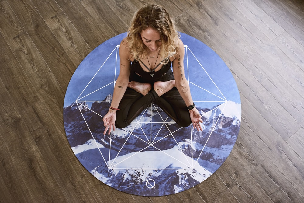 woman meditating in center of round mat