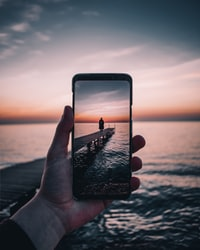 smartphone displaying person standing on dock during golden hour