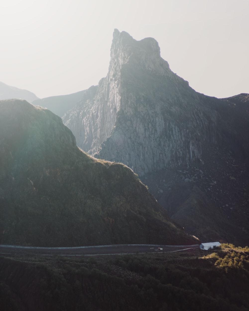vehicle running on road beside mountain