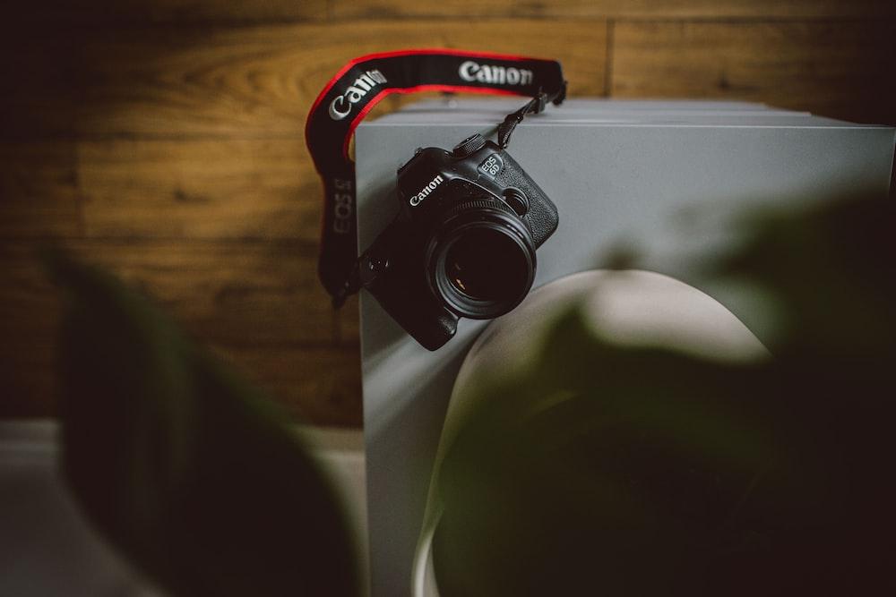 black Canon DSLR camera on white board