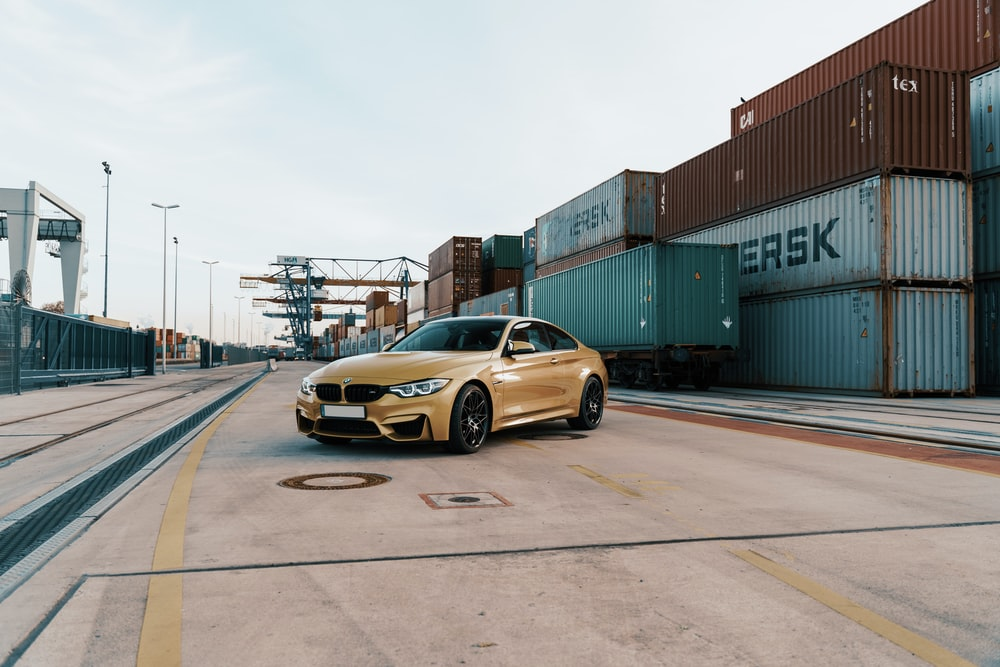 yellow BMW sedan parked near containers during daytime