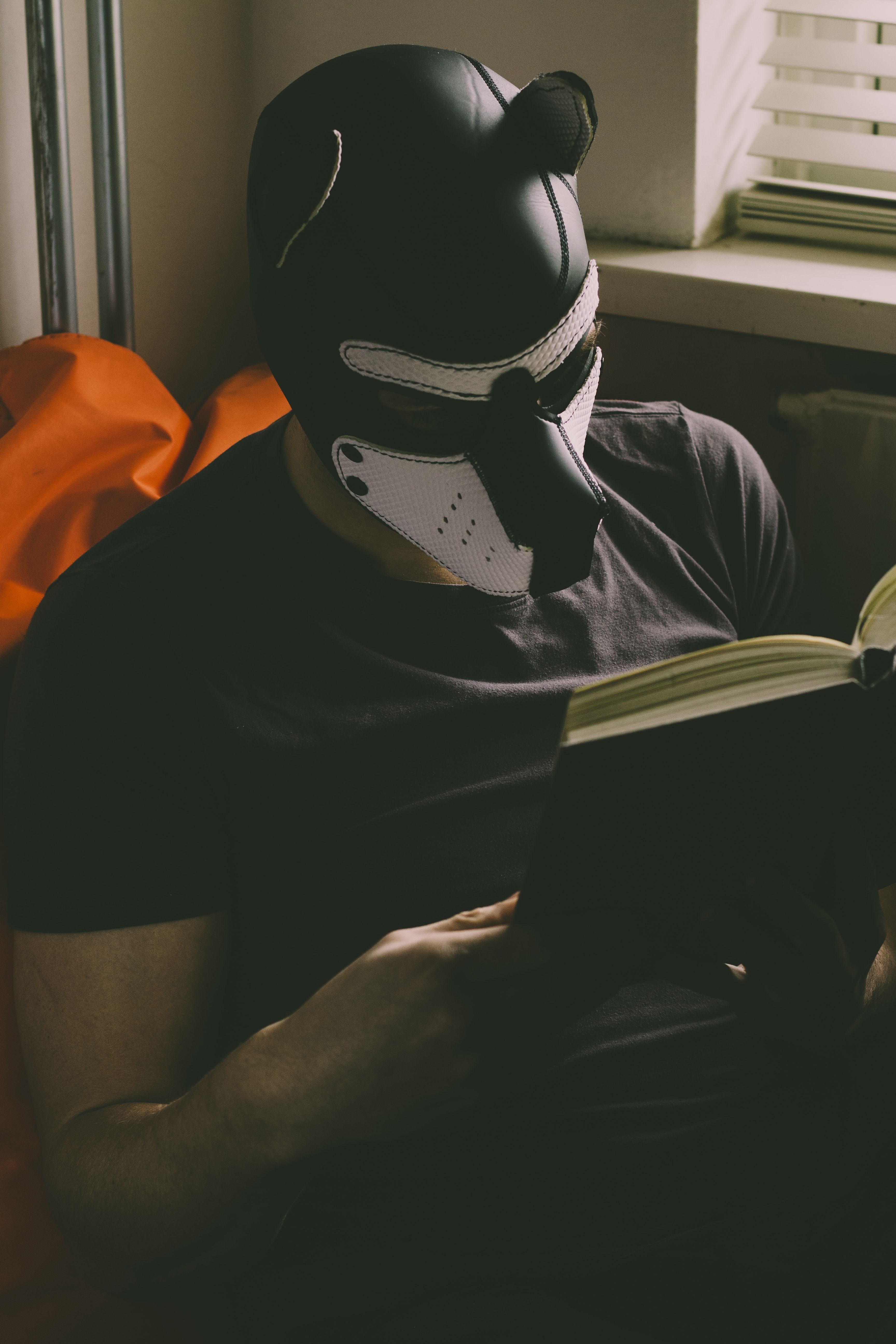 man wearing black and white mask reading book inside room