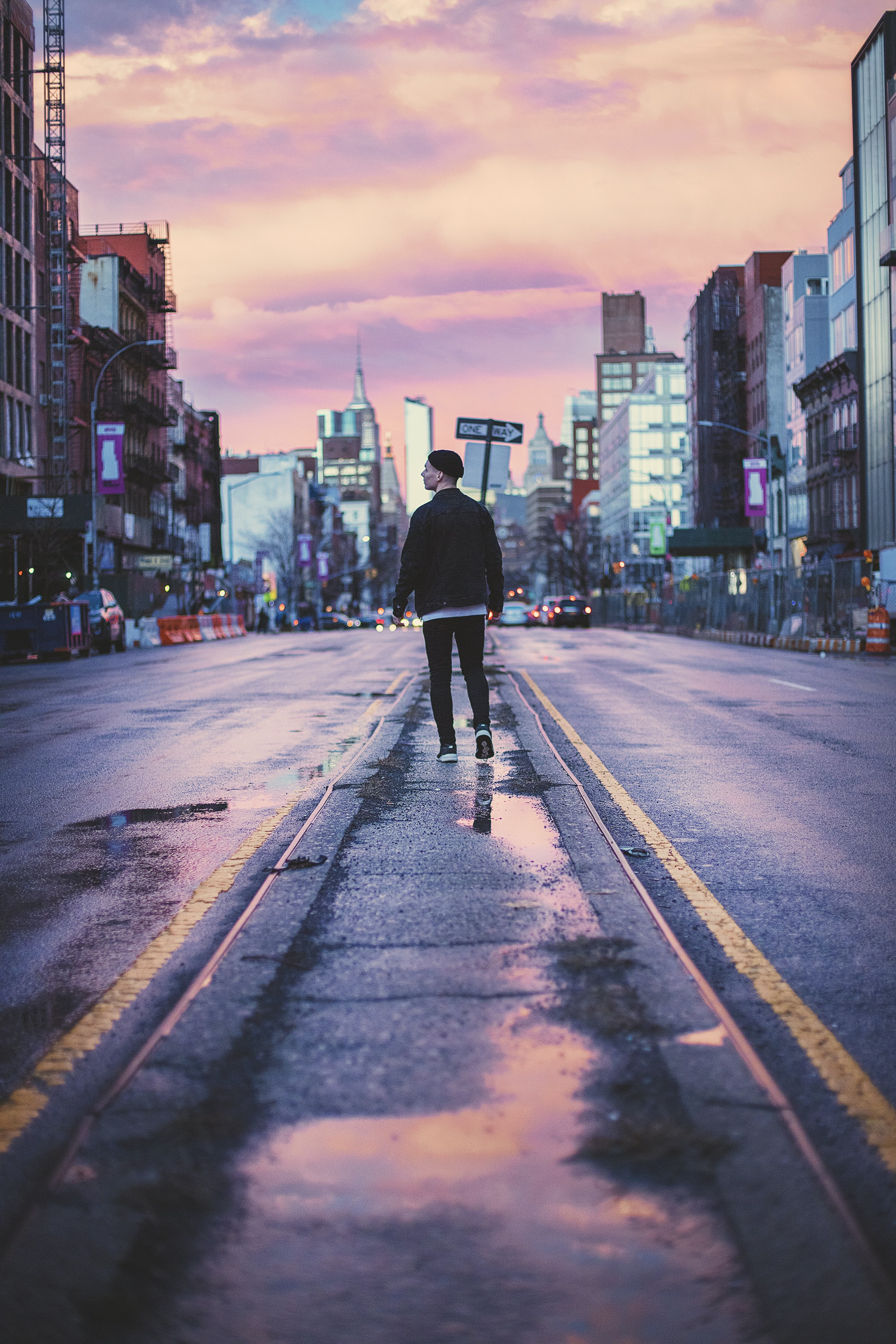 man walking at the middle of the street