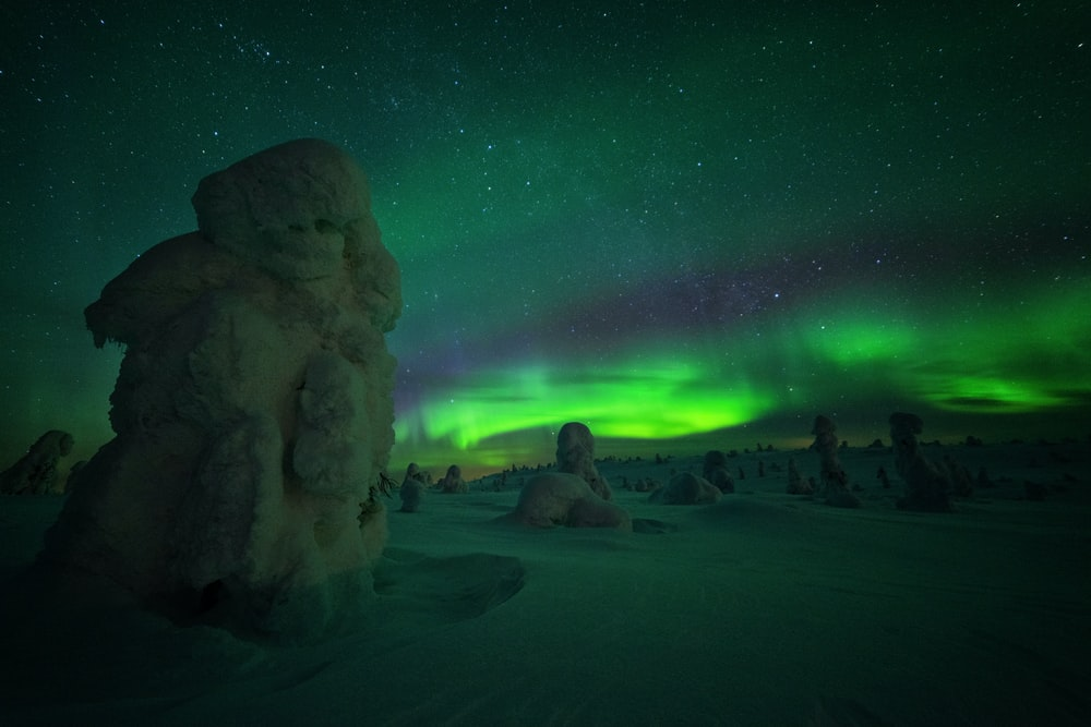stone formations covered with snow at night during Northern lights