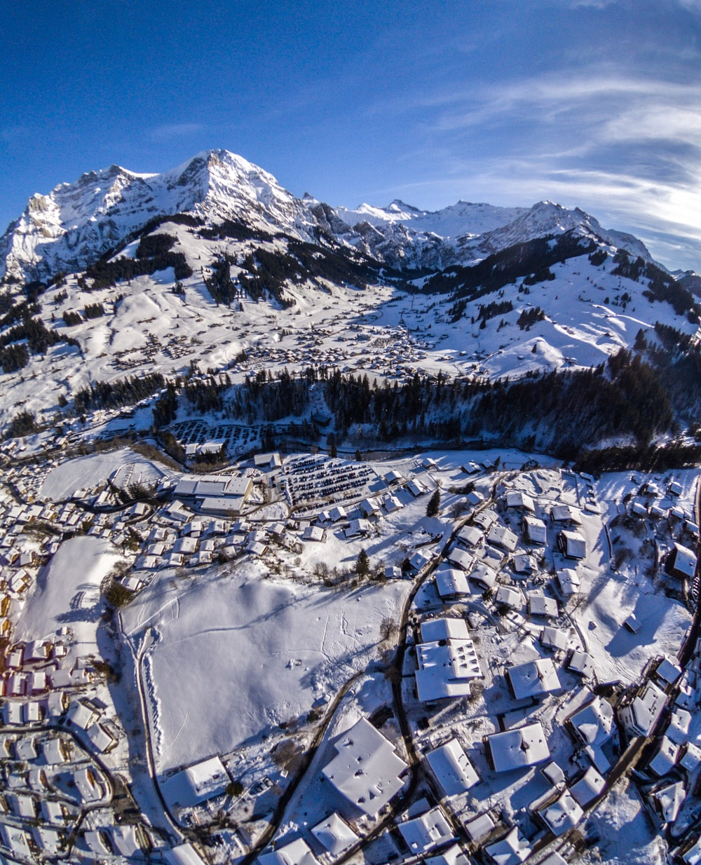 snow capped village near mountain during daytime