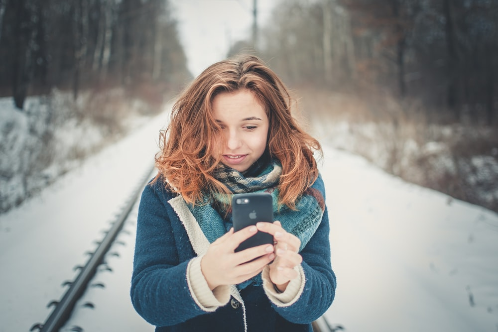 woman holding phone standing on trail