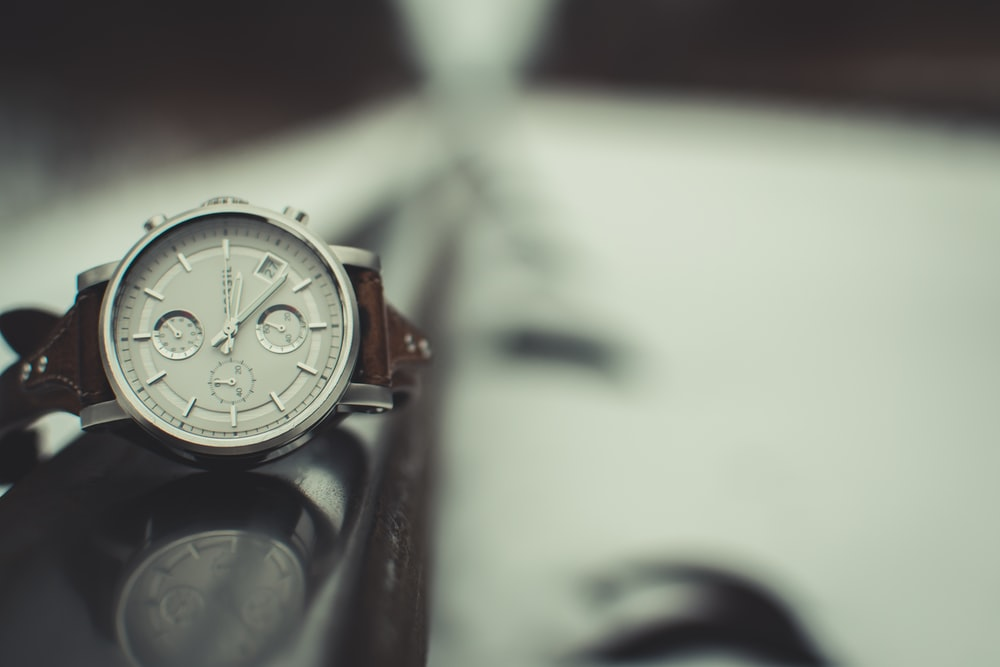 round silver-colored chronograph watch with brown band
