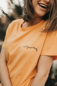smiling woman wearing orange crew-neck t-shirt