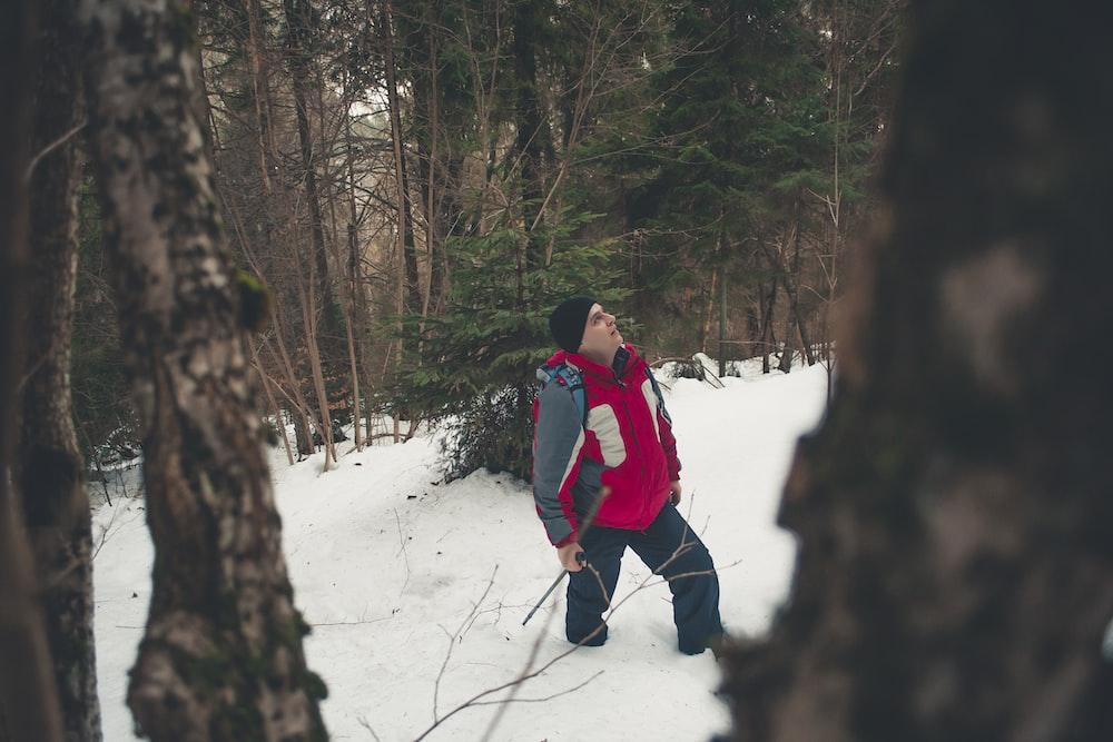 man walking on snow near trees during daytime