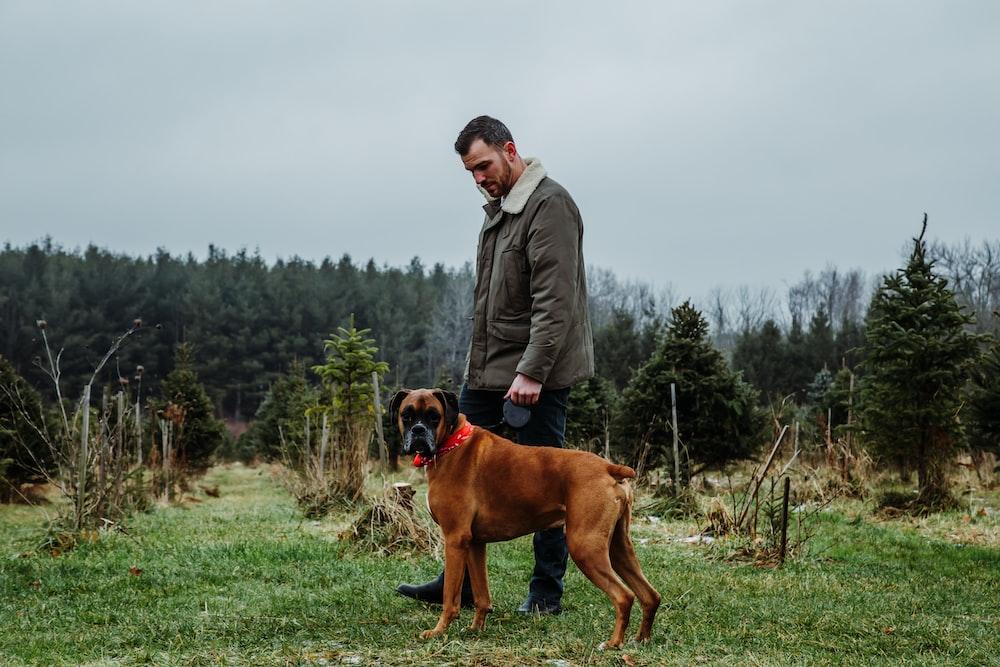 man beside tan dog