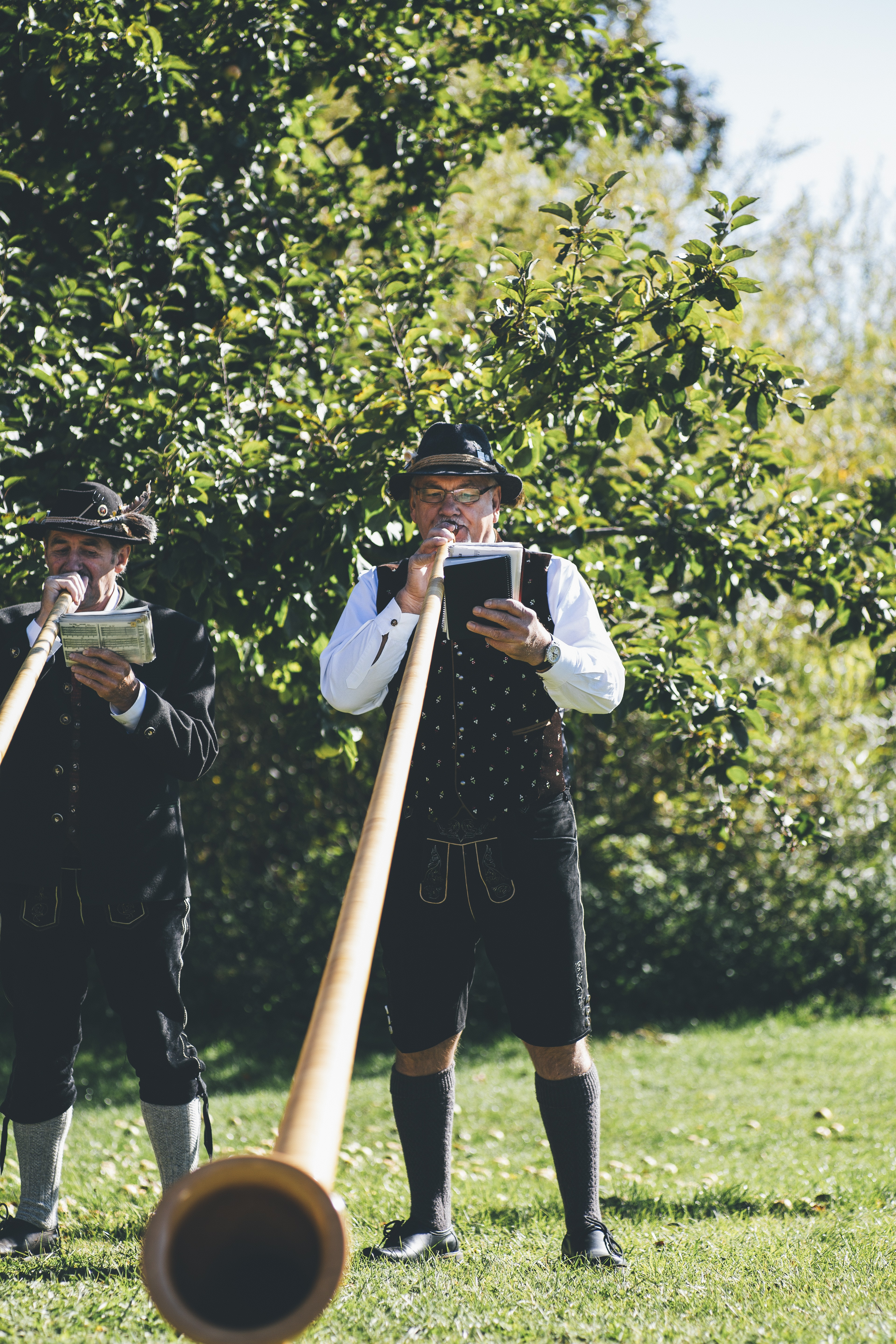 two men playing brown wind instrument while holding books during daytime