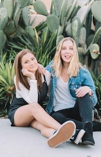 two women sitting near green plant