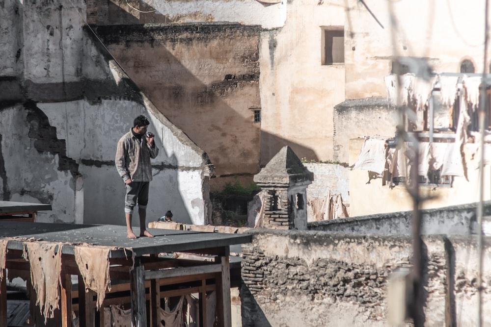 man standing near brown concrete building
