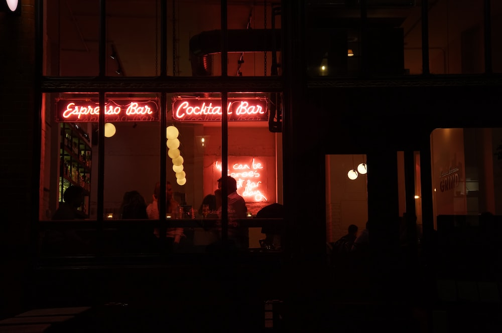 people sitting inside building with red neon signage