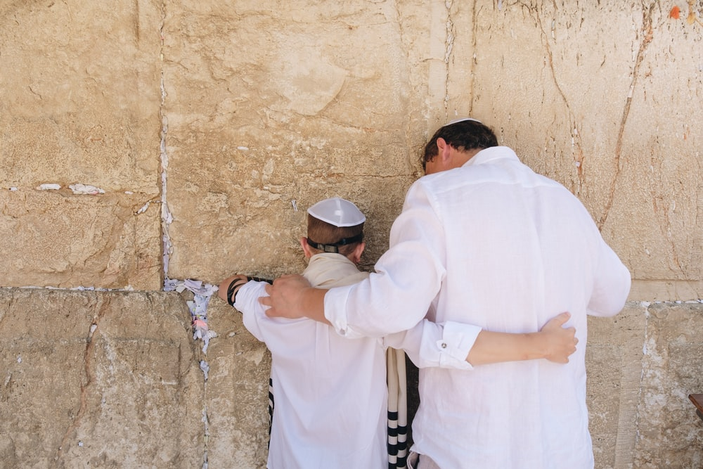 two men in white top standing beside wall