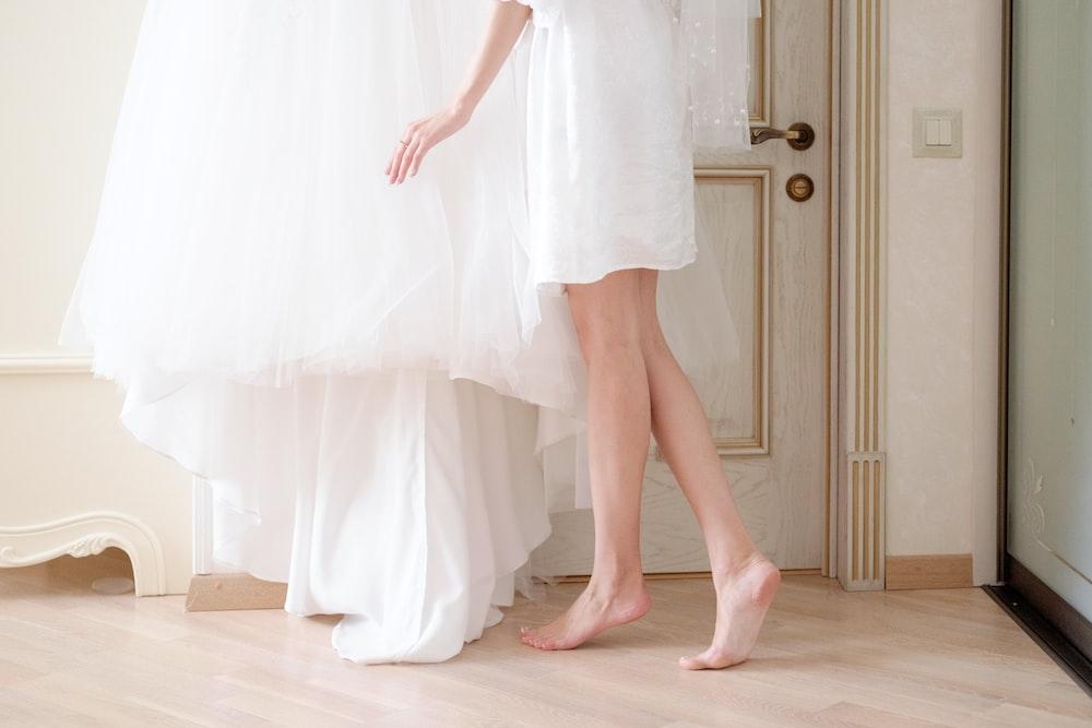 barefoot woman wearing white shirt standing near white dress