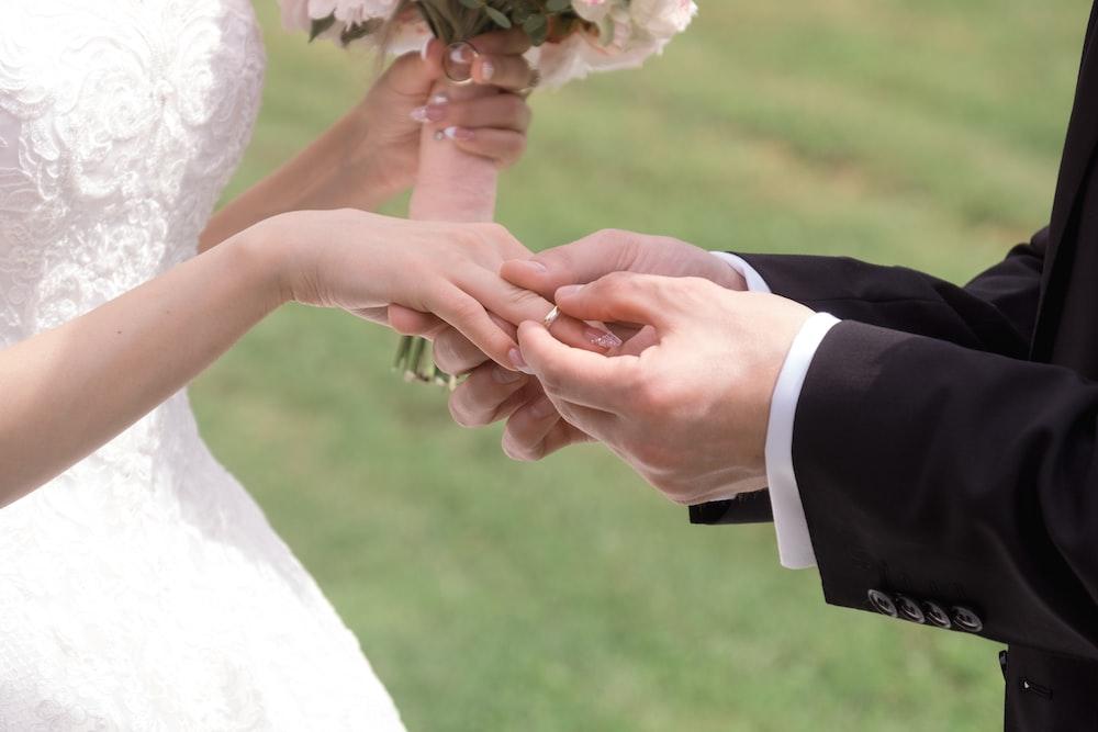 man putting wedding ring on bride during daytime