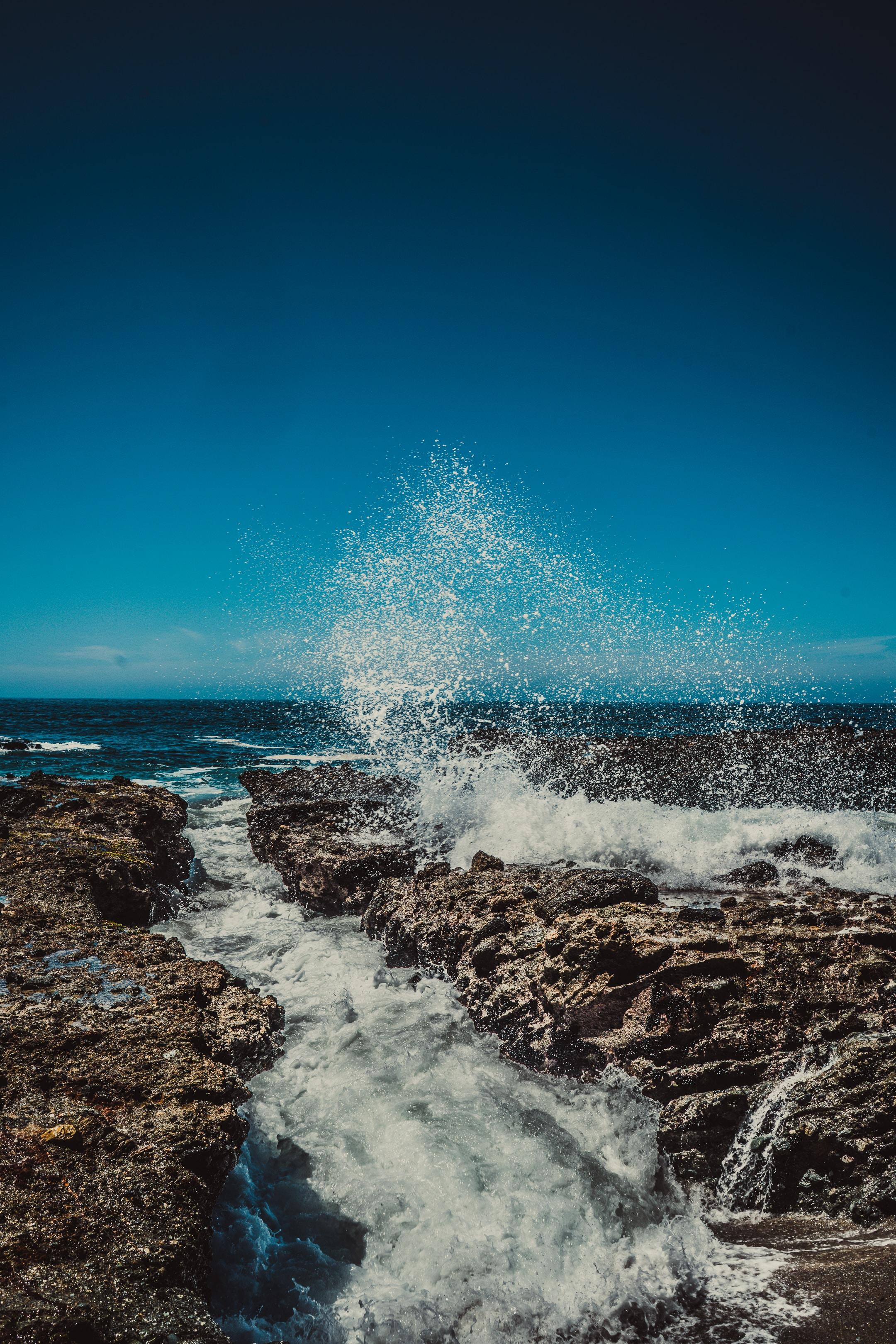 water splashing on rock under blue sky