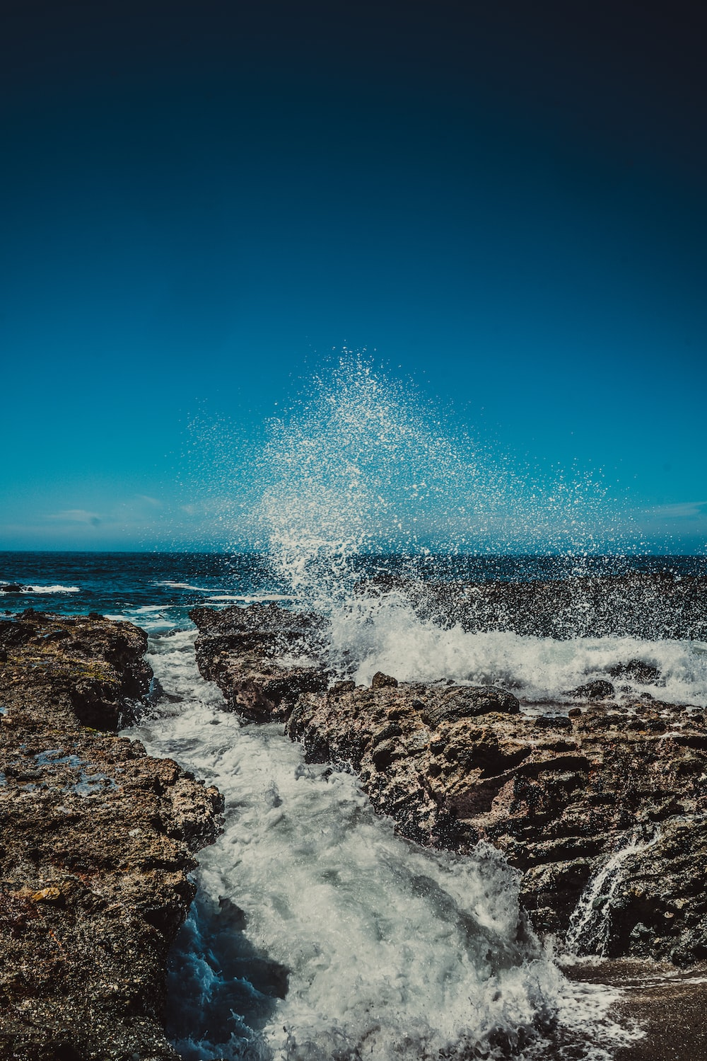 water splashing on rock under blue sky