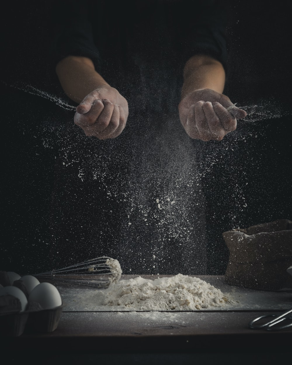 person pouring flour on table beside eggs and whisk