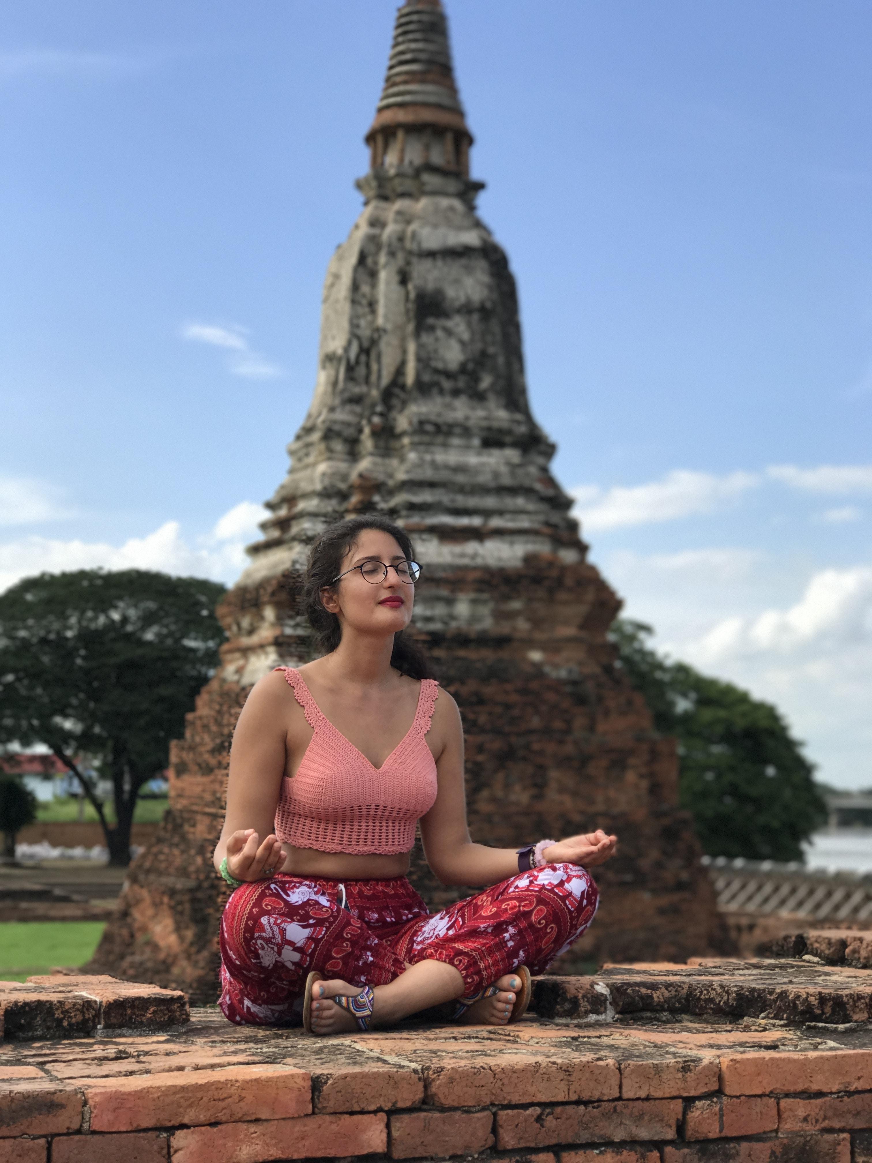 woman doing yoga pose beside landmark