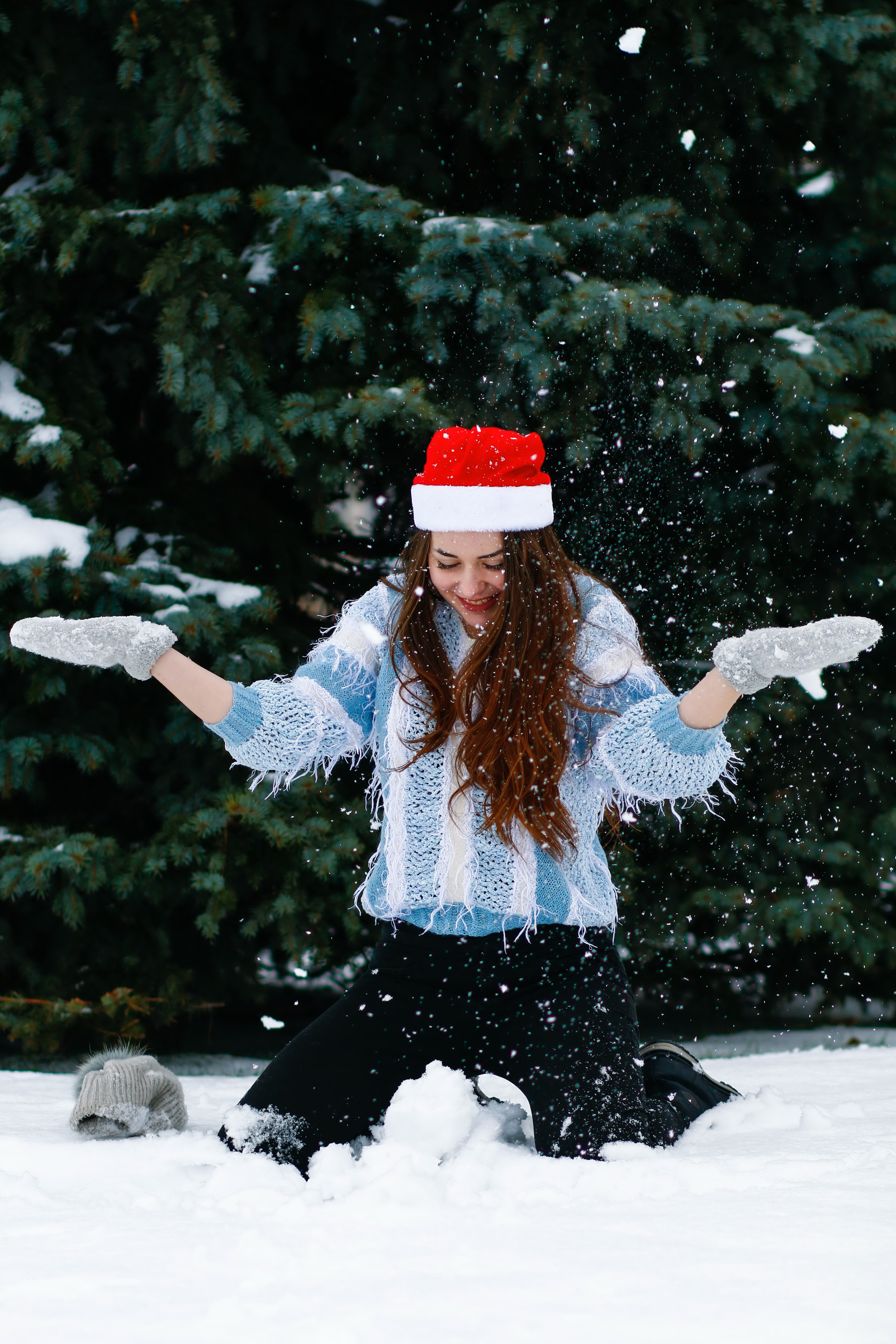 woman in blue sweater playing with white snow near green tree during daytime