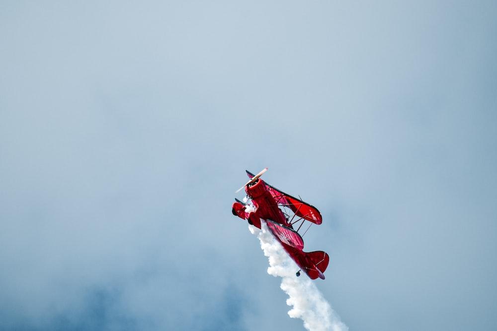 red exhibition plane releasing smoke during daytime