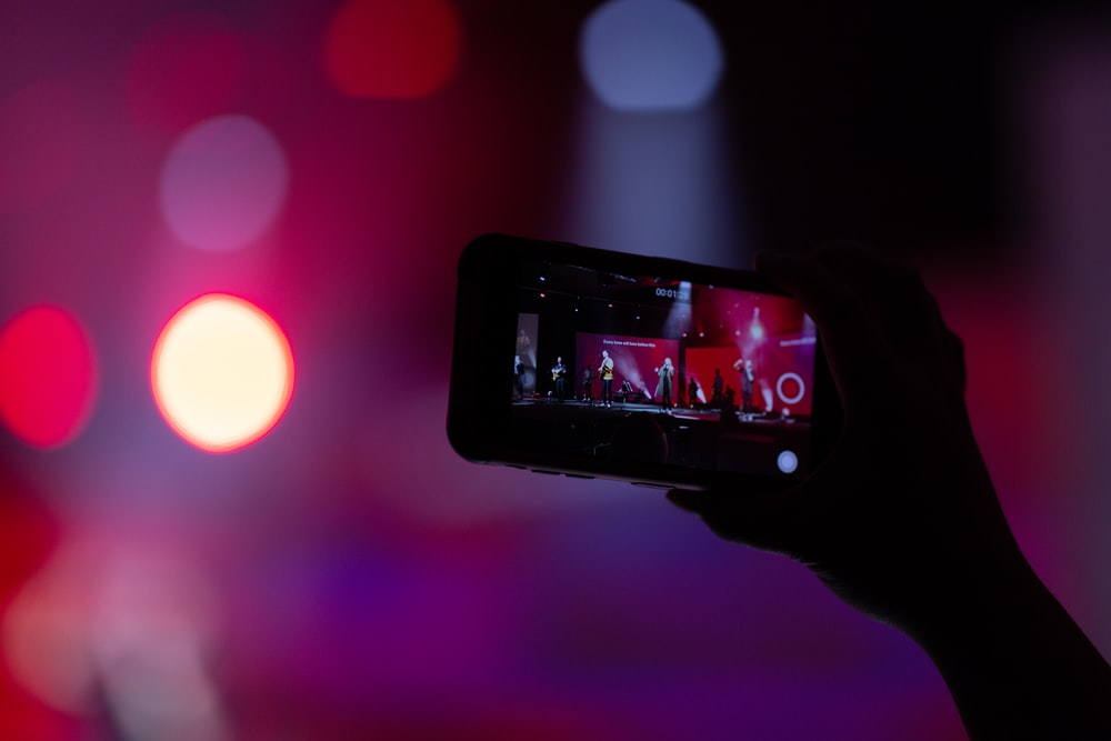 shallow focus photo of person holding smartphone