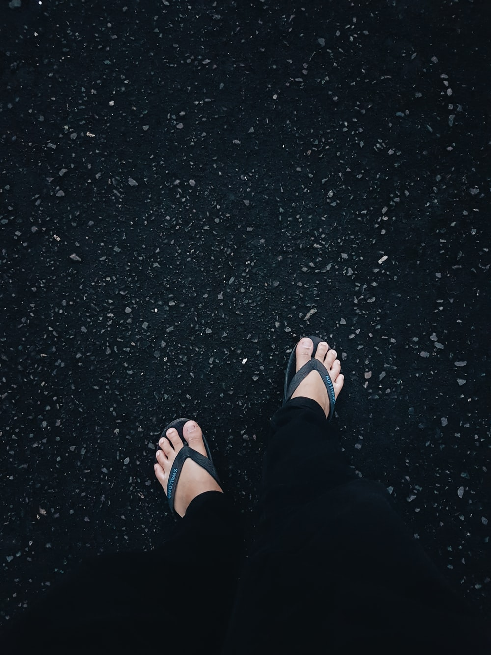person in black flip flops and black pants standing on black asphalt floor