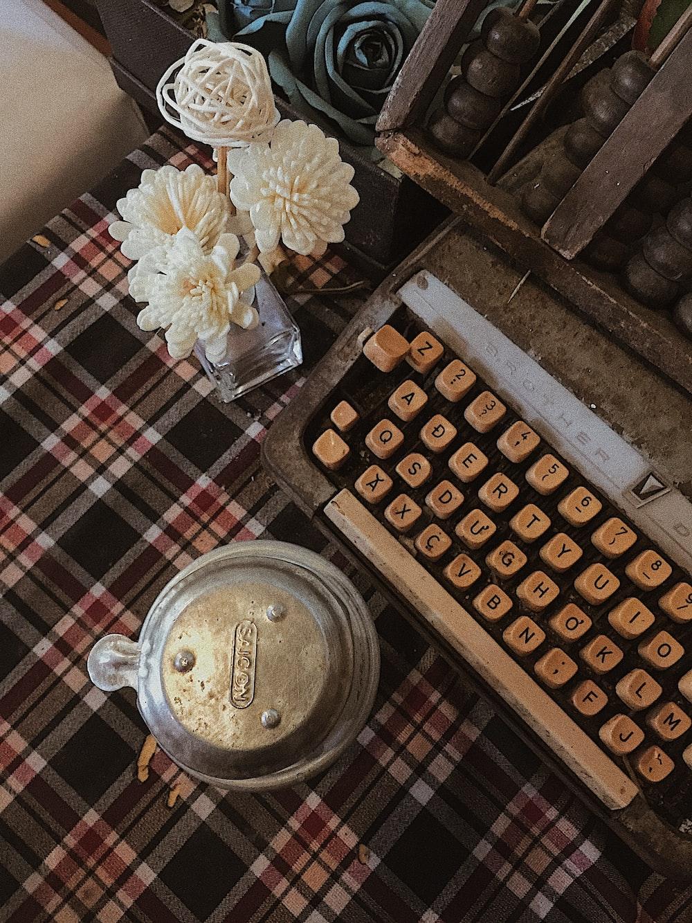 white flower centerpiece beside typewriter