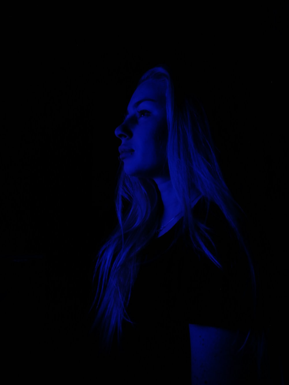 woman wearing t-shirt lighted with blue light