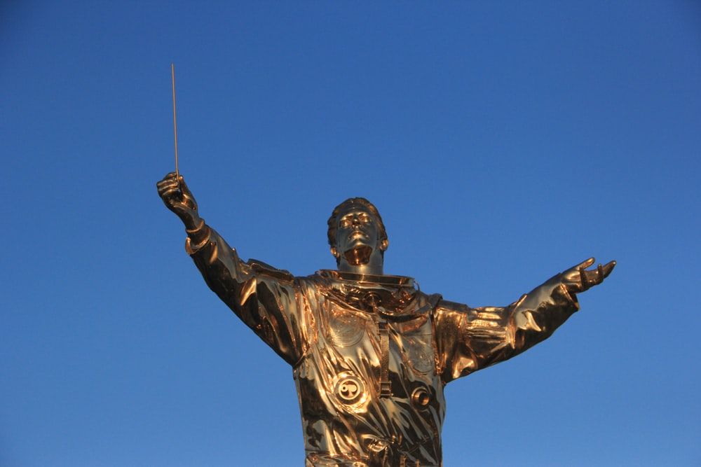 gold-colored man holding stick statue at daytime
