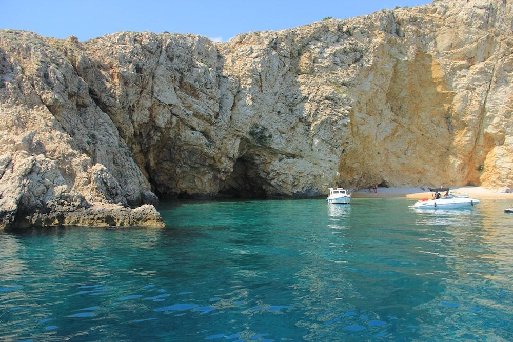 raft and speedboat on sea near rock mountain