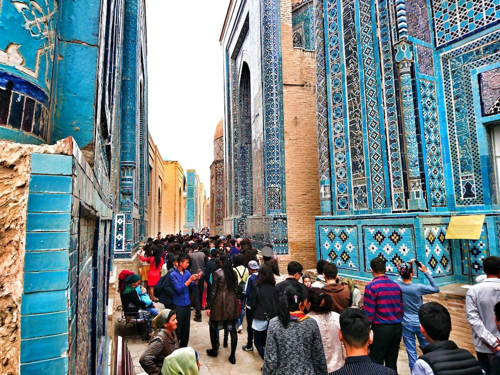 people walking on pathway near blue high-rise buildings
