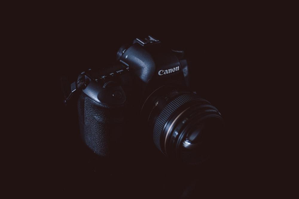 black Canon DSLR camera with black background