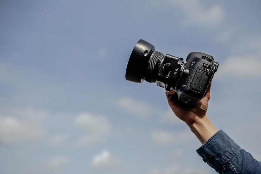 man using his black DSLR camera