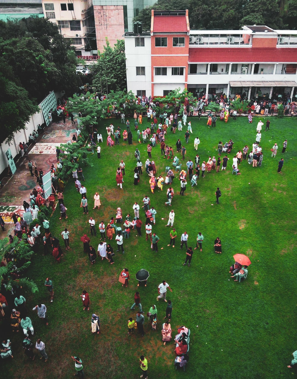 aerial photography of people walking on green field near white and red concrete 3-story building during daytime