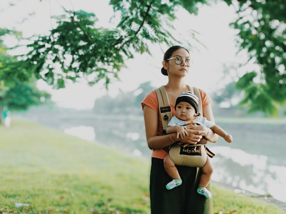 woman carrying his child standing near river