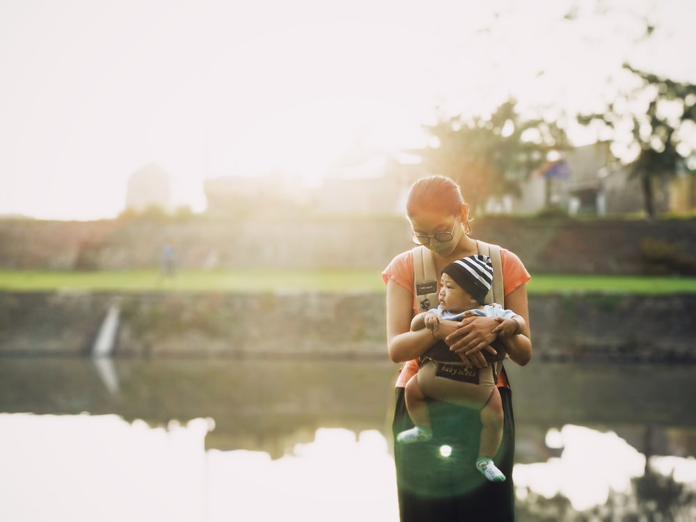 woman carrying a baby with brown carrier while standing near body of water