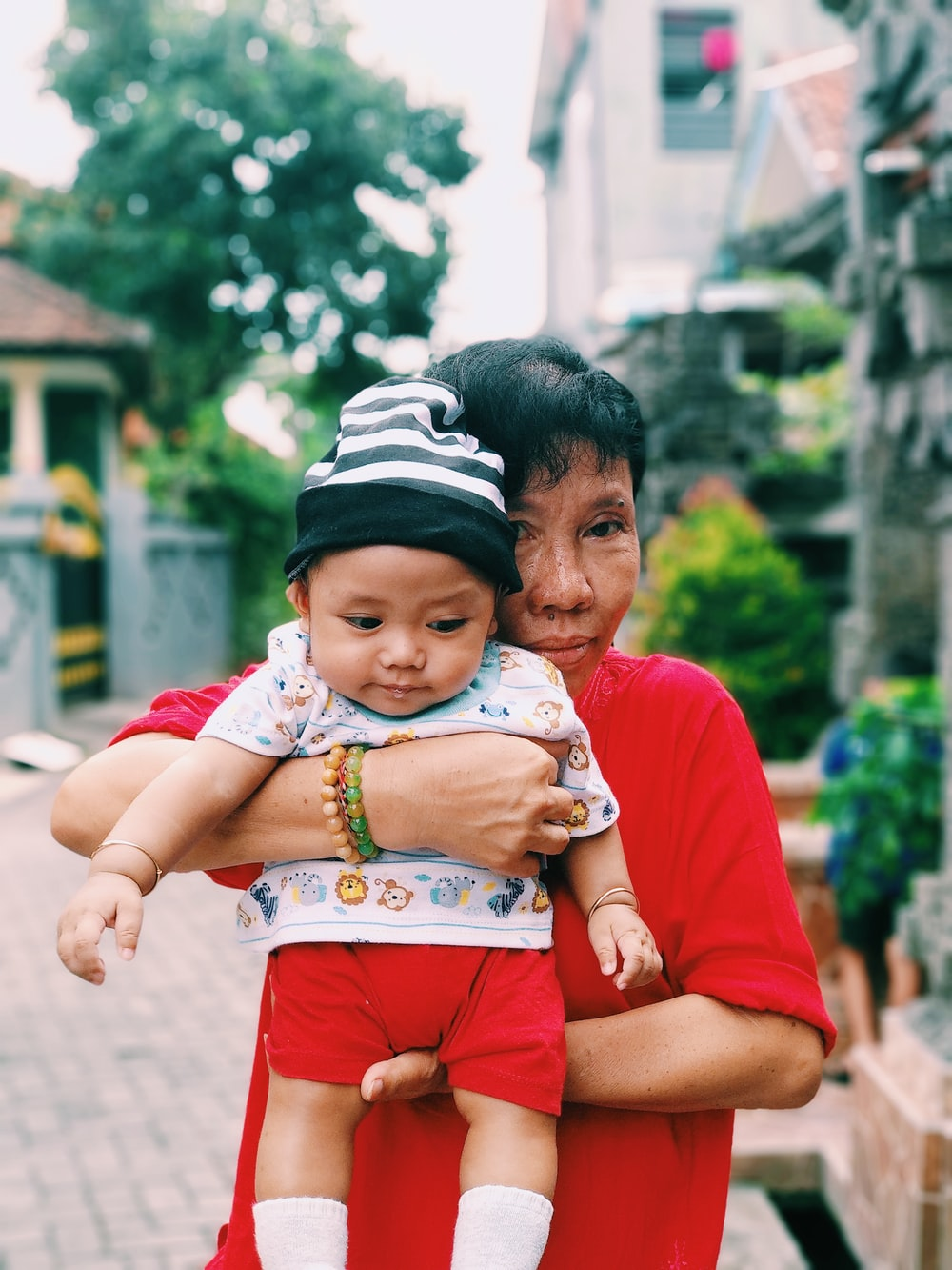 woman carrying a baby near houses at daytime