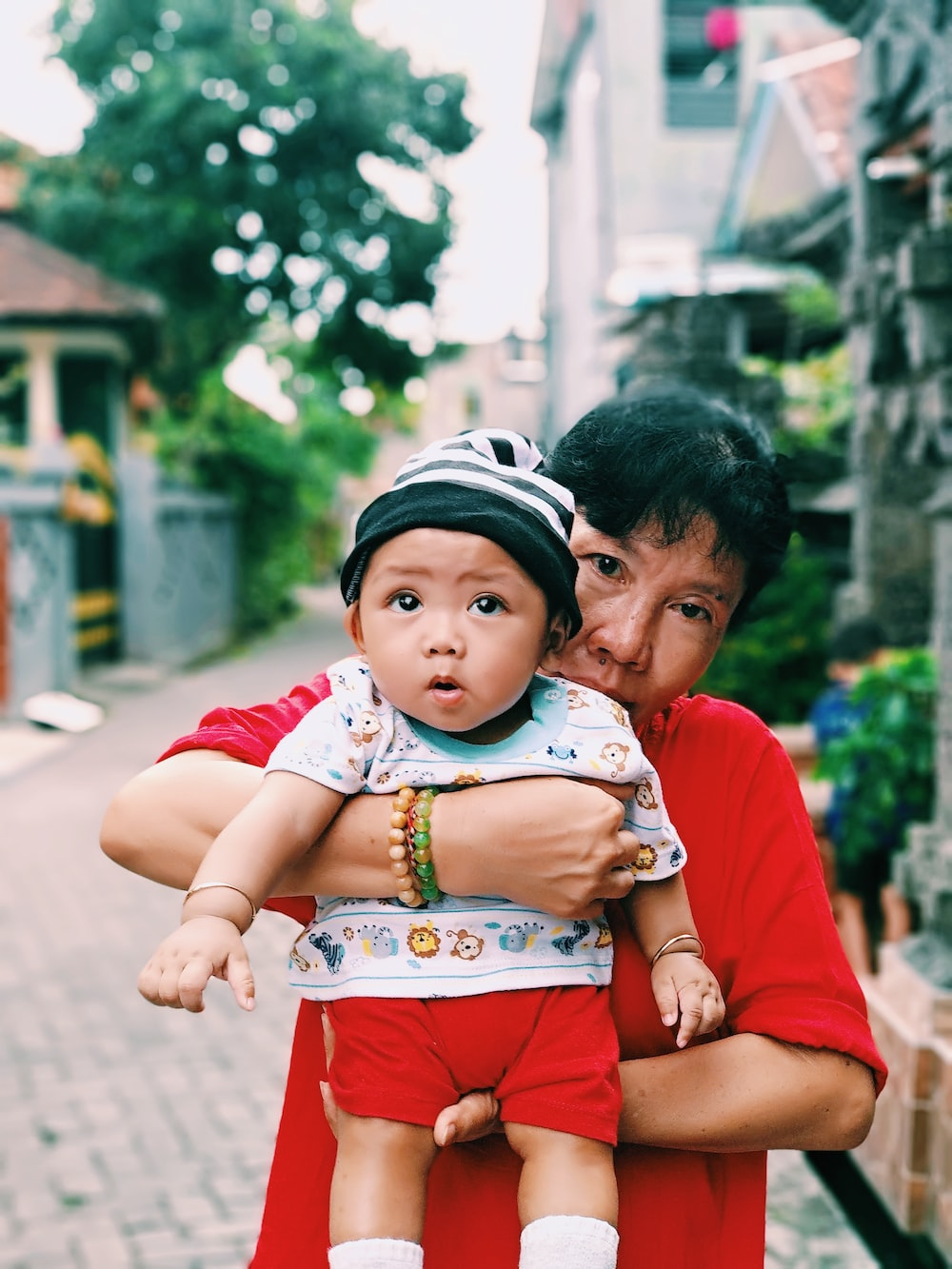 girl wearing red shirt carrying baby outdoor during daytime