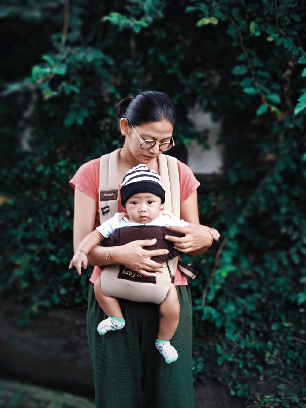 woman holding baby beside green plants