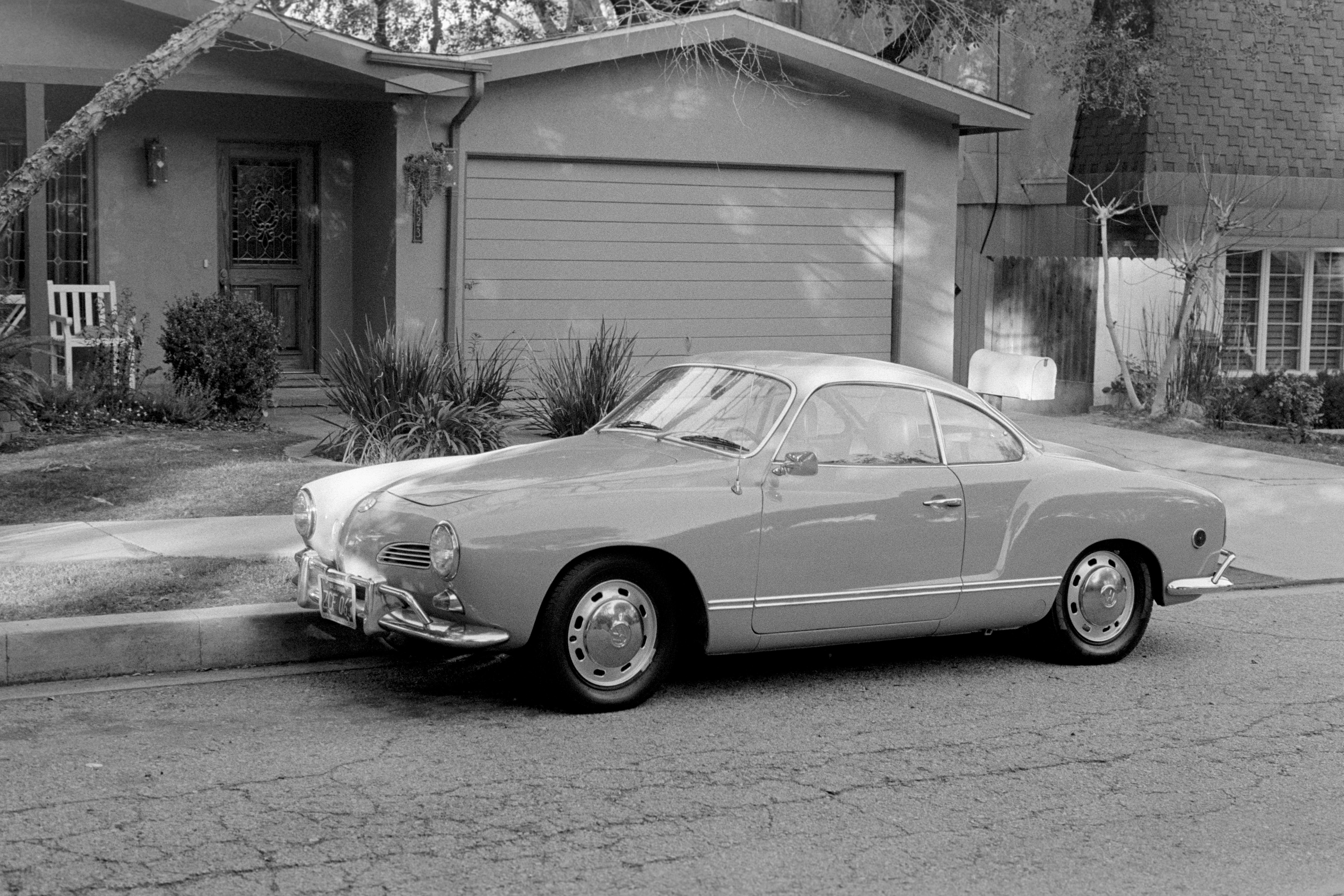 classic coupe park near house in grayscale photo