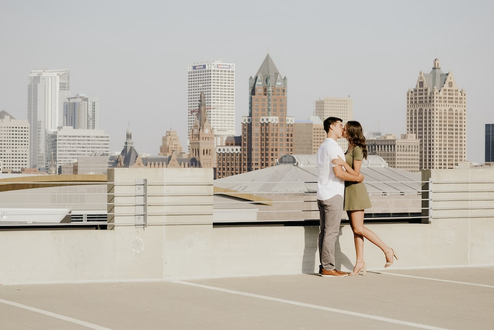 man and woman kissing beside wall