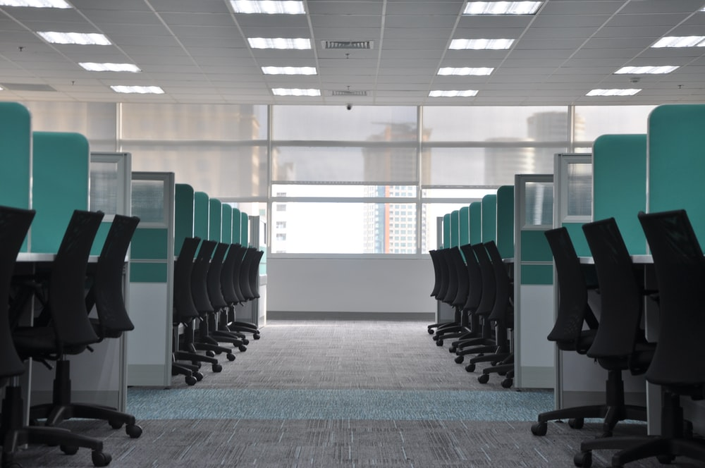 empty black rolling chairs at cubicles