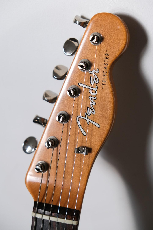brown Fender guitar headstock on white surface