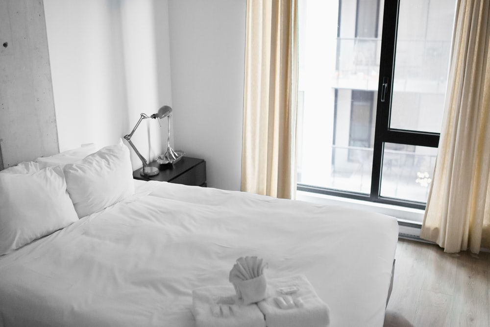 vacant white bed near the window