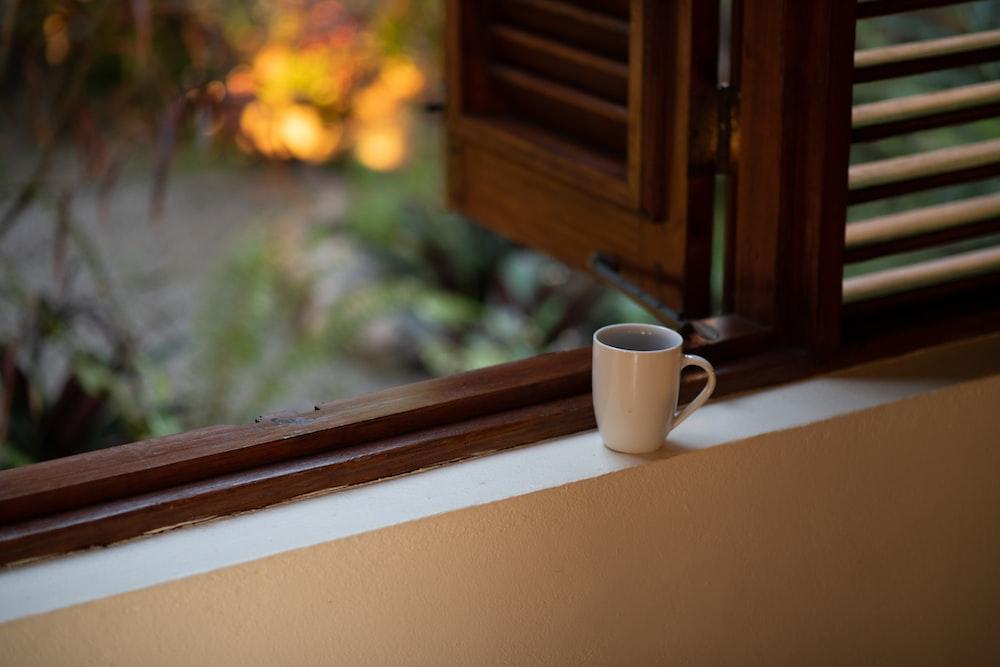 white ceramic mug on white and brown window